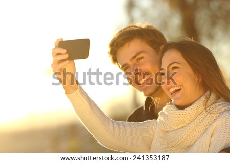 Happy couple taking selfie photo with a smart phone at sunset on the beach - stock photo