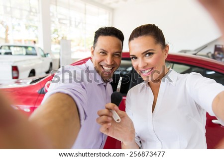 happy couple taking selfie together at dealership after bought new car - stock photo