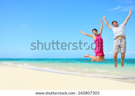 Happy couple tourists jumping on beach vacations. Travel concept of young couple cheering for summer holidays showing success, happiness, and joy on perfect white sand tropical beach under the sun. - stock photo
