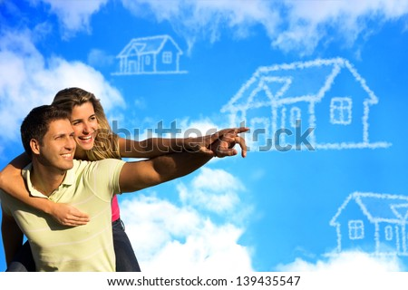 Happy couple under the blue sky enjoying the sun pointing to a house made of clouds. - stock photo