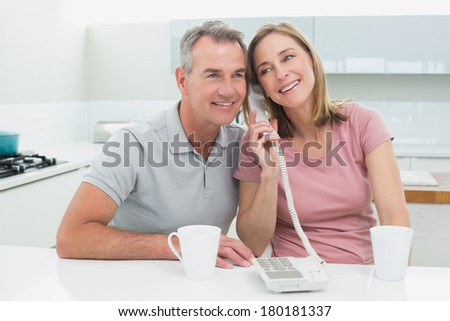 Happy couple using landline phone together in the kitchen at home - stock photo