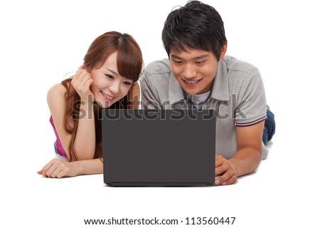 Happy couple using laptop isolated on white background. - stock photo