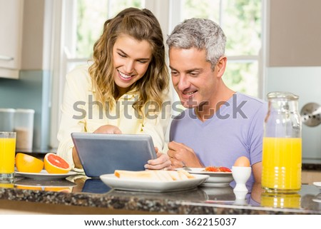 Happy couple using tablet and having breakfast in the kitchen - stock photo