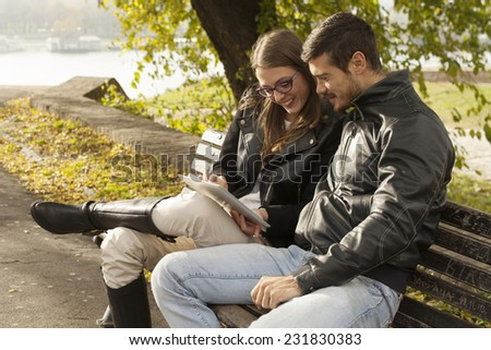 Happy Couple Using Tablet Computer Outdoor In Park On Bench - stock photo