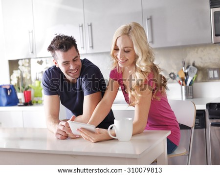 happy couple using tablet pc to shop online or watch videos in kitchen at breakfast - stock photo