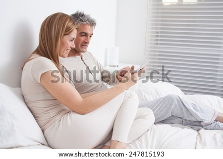 Happy couple using the ipad in the bed - stock photo