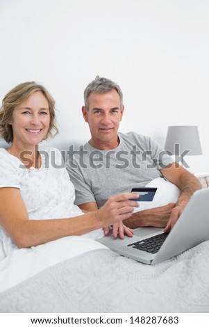 Happy couple using their laptop to buy online smiling at camera at home in bedroom - stock photo