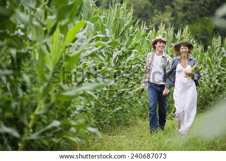 Happy Couple Walking in Corn Field - stock photo