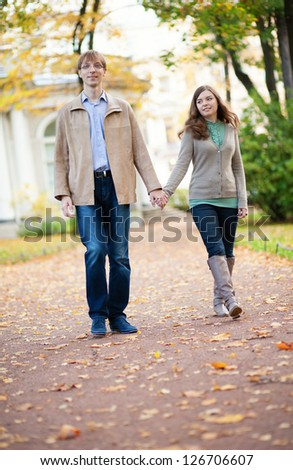 Happy couple walking in park on a fall day - stock photo