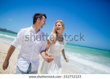 Happy Couple Walking On Beach. - stock photo