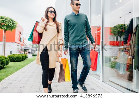 Happy couple walking with shopping bags - stock photo