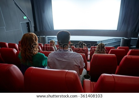 happy couple watching movie in theater or cinema - stock photo