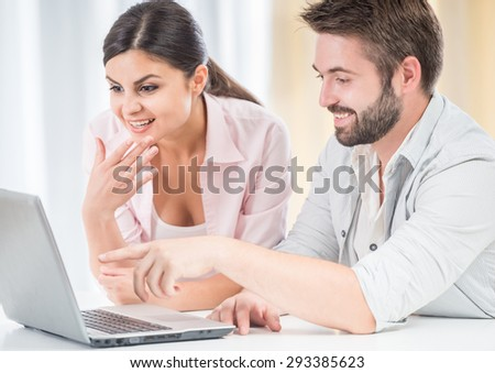 Happy couple watching movie on laptop, sitting at the table at home. - stock photo
