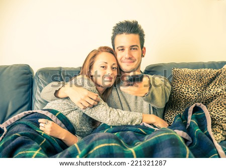 Happy couple watching television on the couch - family,recreation,leisure,togetherness concept - stock photo