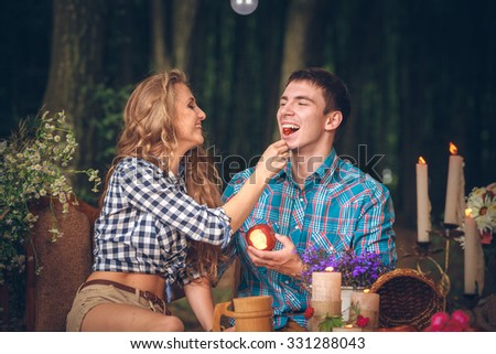 Happy couple with an apple and cherry outdoor - stock photo