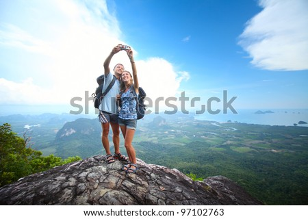Happy couple with backpacks making a snapshot of themselves on top of a mountain - stock photo