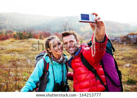 Happy couple with backpacks taking self picture - stock photo