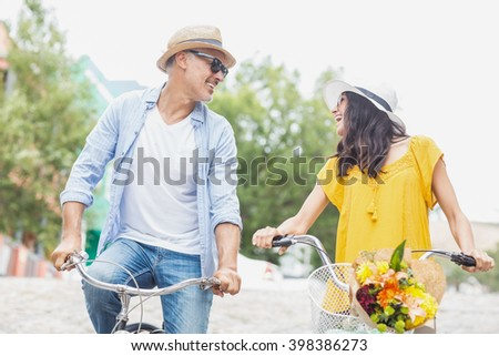 Happy couple with bicycles looking at each other - stock photo