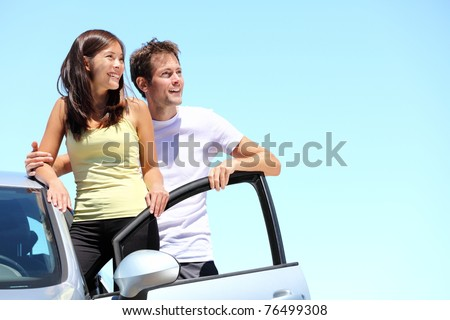 Happy couple with car. Young interracial couple standing with car looking at the sky with copy space. - stock photo