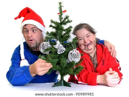 happy couple with down syndrome near a Christmas tree. Isolated over white background - stock photo