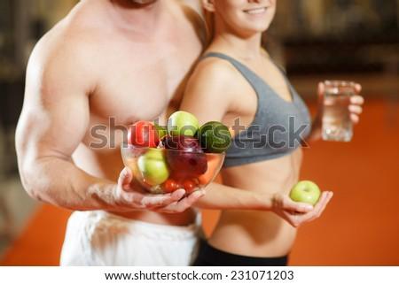 Happy couple with fruits and vegetables - stock photo