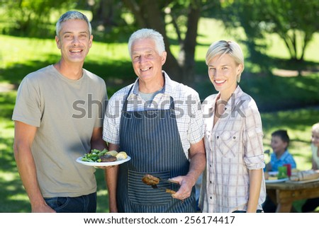 Happy couple with grandfather doing barbecue on a sunny day - stock photo