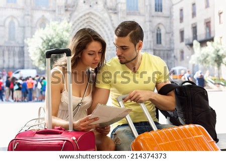 Happy couple with map chasing city streets and looking for hotel - stock photo