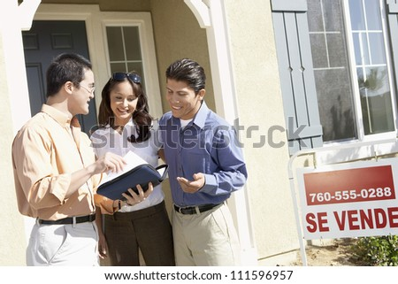 Happy couple with real estate agent in front of new house - stock photo
