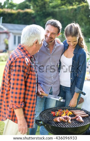 Happy couple with senior man preparing food on barbecue in back yard - stock photo