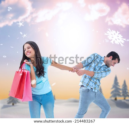 Happy couple with shopping bag against snowy landscape with fir trees - stock photo