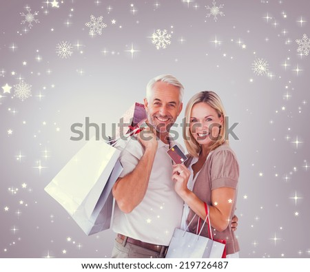 Happy couple with shopping bags and credit card against grey vignette - stock photo