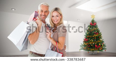 Happy couple with shopping bags and credit card against home with christmas tree - stock photo