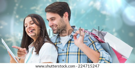 Happy couple with shopping bags and tablet against blurred christmas background - stock photo