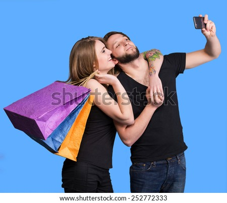 Happy couple with shopping bags taking selfie on a blue background - stock photo