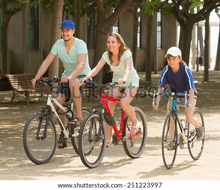 Happy couple with teenager son cycling through city in summer day - stock photo