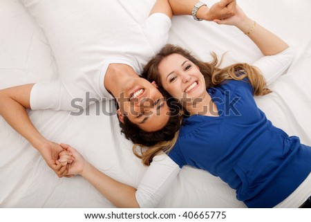 Happy couple with their heads together at home - stock photo