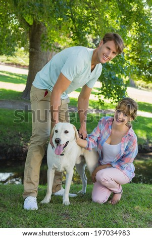 Happy couple with their labrador in the park smiling at camera on a sunny day - stock photo