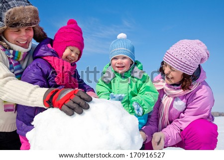 Happy couple with two children making big snowman - stock photo