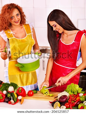 Happy couple women preparing food at kitchen. - stock photo