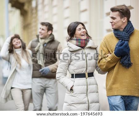 Happy couples in warm clothing enjoying vacation - stock photo