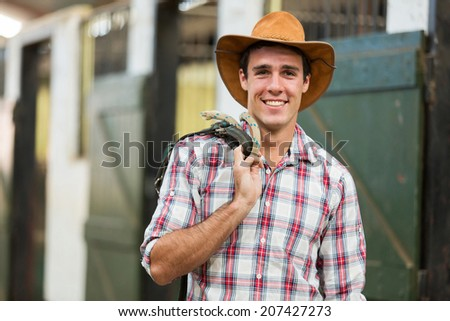 happy cowboy carrying reins of a horse inside stables - stock photo