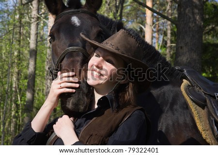 Happy cowgirl in hat hugging her horse - stock photo