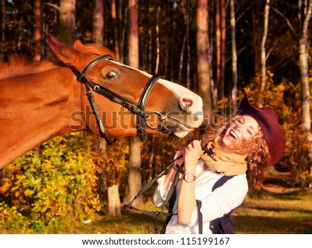 Happy cowgirl with her red horse. - stock photo