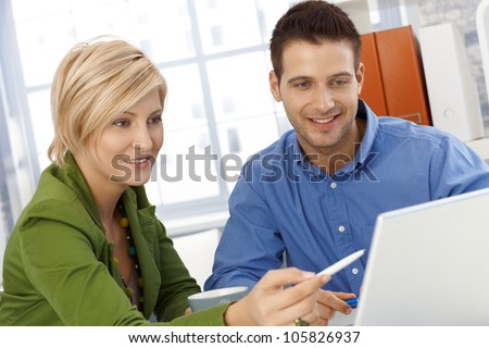Happy coworkers working together, discussing work, using computer, smiling. - stock photo