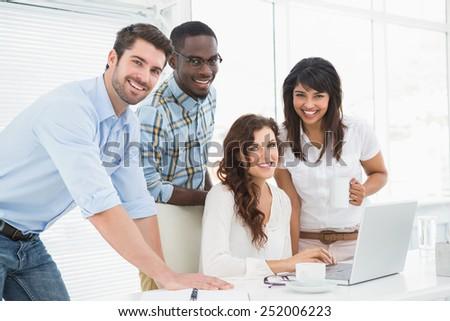 Happy coworkers working together with laptop in the office - stock photo