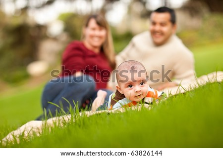 Happy Crawling Baby Boy and Mixed Race Parents Playing in the Park. - stock photo