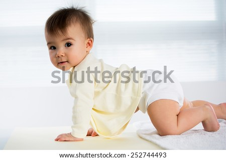 Happy crawling baby. Side view - stock photo