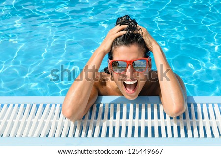 Happy crazy woman in resort pool on holidays. Funny happy girl face expression with red sunglasses on summer hot day. Reflection of beach and palms in glasses. - stock photo