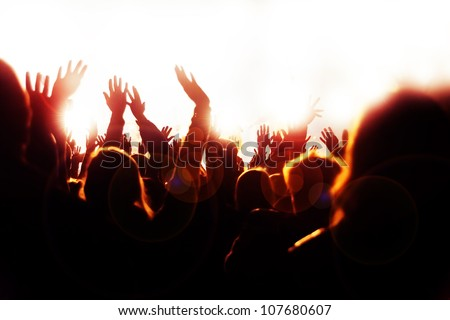 Happy crowd waving hands and sheering at the music concert - stock photo