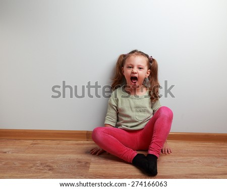 Happy crying kid with open mouth sitting on the floor in fashion clothes - stock photo